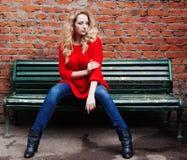摆在时髦红色毛线衣、牛仔裤和黑起动的一个难以置信的白肤金发的女孩坐长凳对砖墙 免版税库存照片