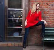 摆在时髦红色毛线衣、牛仔裤和黑起动的难以置信的白肤金发的女孩 室外 Streetslyle 图库摄影