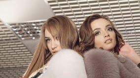摆在时兴的富有的精品店的皮大衣的两个女孩 迟缓地 股票录像