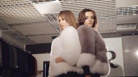 摆在时兴的富有的精品店的皮大衣的两个模型 股票录像