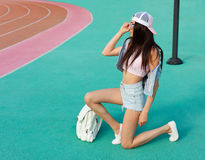 摆在时兴的成套装备和太阳镜的一个体育场的年轻美丽的深色的妇女有一面美国国旗的 方式 Patrotis 免版税库存照片