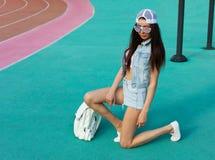 摆在时兴的成套装备和太阳镜的一个体育场的年轻美丽的深色的妇女有一面美国国旗的 图库摄影