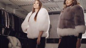 摆在时兴的精品店的皮大衣的两个富有的模型 股票视频