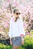 摆在春天背景的美丽的年轻十几岁的女孩 免版税图库摄影