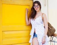 摆在有一个黄色门的一个老房子外的时兴的夏天成套装备的一个美丽的女孩在古城 免版税库存照片