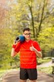 摆在有一张蓝色瑜伽席子的春天公园的红色T恤杉的年轻体育人 他的手展示类 库存图片