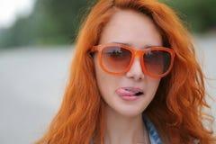 摆在有她的舌头的橙色太阳镜的年轻红发妇女 免版税库存照片