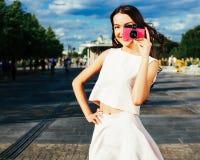 摆在有拍照片的一台桃红色葡萄酒照相机的街道上的夏天明亮的成套装备的一个惊人的亚裔女孩 免版税库存图片