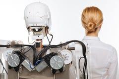 摆在有机器人的一个实验室的热忱的精采科学家 免版税库存照片