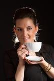 摆在有杯子的演播室的美丽的妇女画象coffe 免版税库存图片