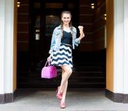 摆在有桃红色袋子和多彩多姿的冰淇凌的一件夏天礼服和牛仔布夹克的美丽的时兴的女孩 室外 图库摄影