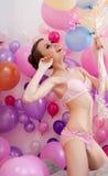 摆在有气球的女用贴身内衣裤的性感的亭亭玉立的模型 免版税库存照片