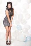 摆在有气球背景的女性时装模特儿 免版税库存照片