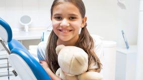 摆在有玩具熊的牙医办公室的愉快的微笑的女孩画象  免版税图库摄影