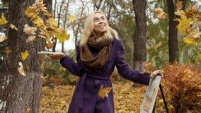 摆在有画架的落的叶子中的少女艺术家在秋天公园 库存照片