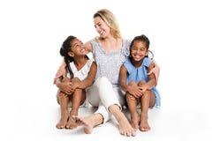摆在有白母亲的一个白色背景演播室的蓬松卷发双孩子 免版税库存图片