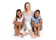 摆在有白母亲的一个白色背景演播室的蓬松卷发双孩子 库存照片