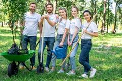 摆在有的公园的年轻志愿者喷壶铲起犁耙和独轮车 库存图片