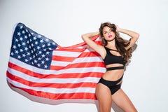 摆在有美国国旗的比基尼泳装的美丽的年轻性感的女孩 免版税库存照片