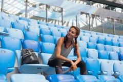 摆在有背包的体育场的性感的体育女孩 有的健身女孩体育在黑绑腿计算坐在Th的位子 图库摄影