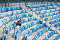 摆在有背包的体育场的性感的女孩 有的健身女孩体育在黑绑腿计算坐在stad的位子 库存照片