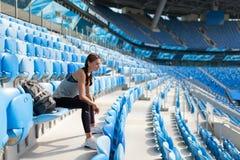 摆在有背包的体育场的性感的女孩 有的健身女孩体育在黑绑腿计算坐在stad的位子 免版税库存图片
