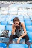 摆在有背包的体育场的性感的女孩 有的健身女孩体育在黑绑腿计算坐在stad的位子 图库摄影