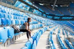 摆在有背包的体育场的性感的女孩 有的健身女孩体育在黑绑腿计算坐在stad的位子 免版税图库摄影