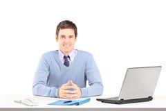 摆在有膝上型计算机和其他办公室工作人员的一张书桌上的微笑的男性 免版税库存照片