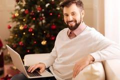 摆在有膝上型计算机的沙发的快乐的人在膝部 免版税库存照片