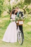 摆在有花梢的公园的肉欲的年轻新婚佳偶夫妇装饰了自行车 库存照片