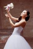 摆在有花的演播室的深色的新娘 库存图片