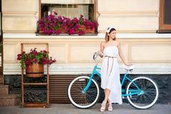 摆在有葡萄酒蓝色减速火箭的自行车的老镇的女孩 库存照片