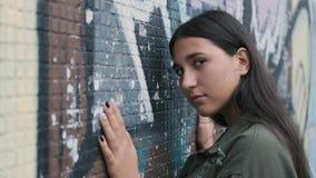 摆在有街道画的墙壁附近的美丽的行家女孩 在墙壁上的手 股票视频