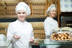 摆在有长方形宝石和小圆面包的面包店的帽子的妇女 库存照片