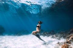 摆在有飞翅的含沙海的妇女freediver 免版税库存照片
