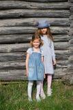 摆在木墙壁的蓝色便衣的两个快乐的姐妹女孩 有效的生活方式 青年时尚 免版税库存照片