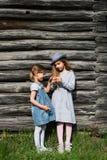 摆在木墙壁的蓝色便衣的两个快乐的姐妹女孩 有效的生活方式 青年时尚 库存图片