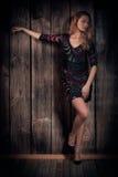 摆在木墙壁背景的一件短的礼服的自然看起来的美丽的夫人 免版税库存图片