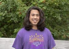 摆在木桥的25岁的Amerasian男性在华盛顿公园树木园,西雅图,华盛顿 免版税库存照片