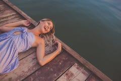 摆在木码头的愉快的女孩 免版税库存图片