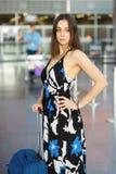 摆在机场的逗人喜爱的妇女 免版税库存图片