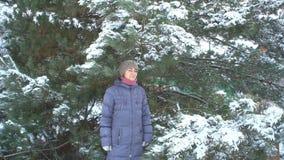 摆在杉木背景的可爱的妇女与雪的在她的冬景花园圣诞快乐和新年快乐 影视素材