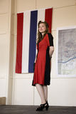 摆在标志前面的20世纪40年代衣物的可爱的妇女 库存照片