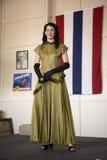 摆在标志前面的20世纪40年代衣物的可爱的妇女 免版税库存图片