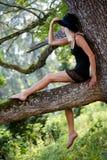 摆在树的年轻可爱的亭亭玉立的妇女 库存图片