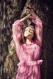 摆在树附近的女孩 库存图片