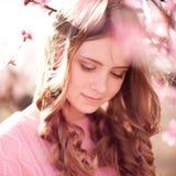 摆在桃子庭院里的微笑的十几岁的女孩 免版税库存照片