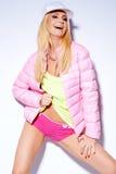 摆在桃红色夹克和短裤的性感的妇女 免版税库存照片