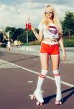 摆在桃红色短裤的葡萄酒溜冰鞋和有一份饮料的白色T恤杉的美丽的性感的白肤金发的女孩在温暖的su的一块玻璃 库存图片